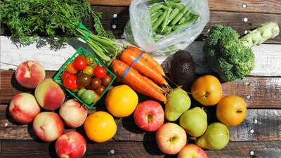 Assortment of local produce (carrots, broccoli, pears, tomatoes)